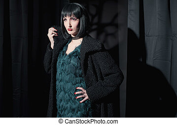 Witch fashion woman wearing black coat. Standing in dark room.