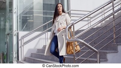 Stylish woman walking down a flight of stairs - Stylish...