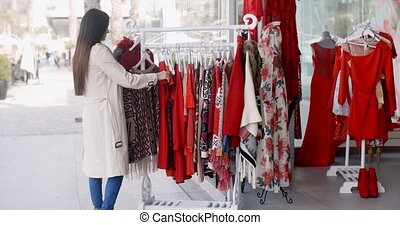 Young woman looking for a colorful red dress searching...