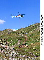 Vertical replenishment with flying helicopter and mountain...