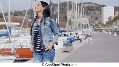 Casual woman enjoying a walk through a marina along a...