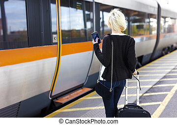 Traveling woman at a outdoor train station terminal - Young...