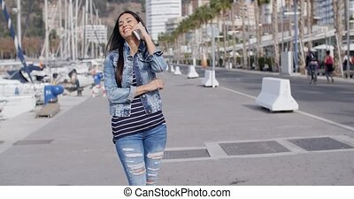 Young woman chatting on her phone in the street