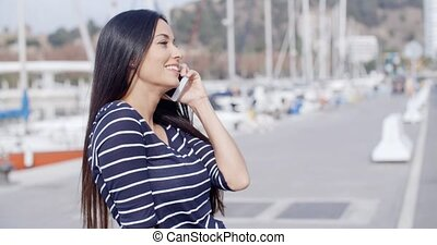 Young woman on a seafront promenade standing chatting on her...