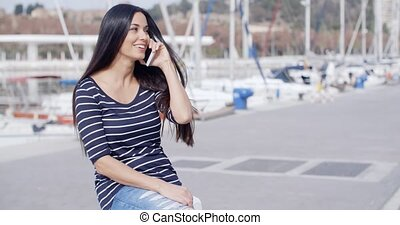 Young woman on a seafront promenade sitting chatting on her...