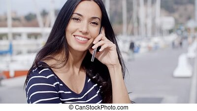Attractive smiling woman using a mobile phone outdoors on an...