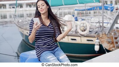 Young woman sitting on a quay checking her mobile