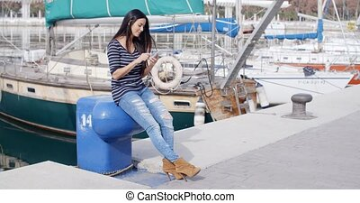 Trendy young woman relaxing at a marine harbour sitting on a...