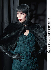 Dark mysterious witch fashion woman. Standing in room with black curtains.