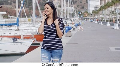Attractive woman walking past a marina - Attractive trendy...