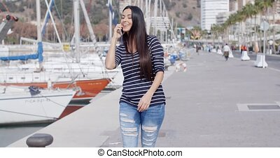 Attractive fashionable young woman on her mobile phone...