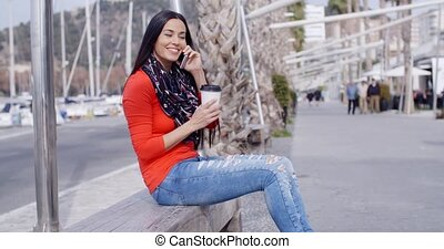 Pretty stylish young woman in colorful fashion sitting...