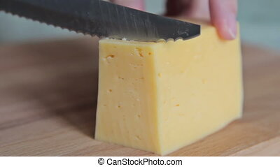 Woman cutting piece of cheese, HD