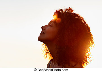 Profile of a woman with afro silhoutted against evening sun...