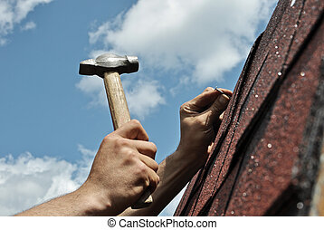 Roof repairs, workers hands with hammer on the sky...