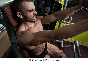 Muscular Male On A Butterfly Machine In Gym - Man Doing...