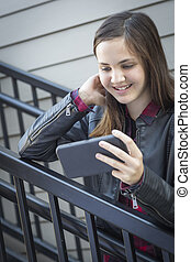 Pretty Young Girl Looking at Smart Phone