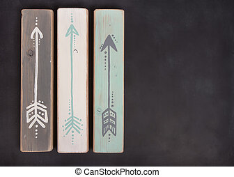 Three hand painted arrows on a blackboard