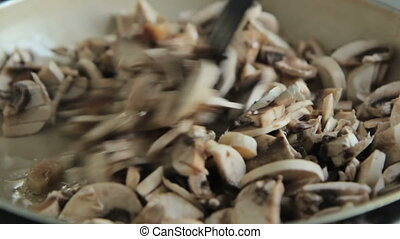 Woman cooking and stirring mushrooms
