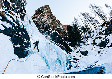 Ice climbing: male climber on a icefall in italian Alps.