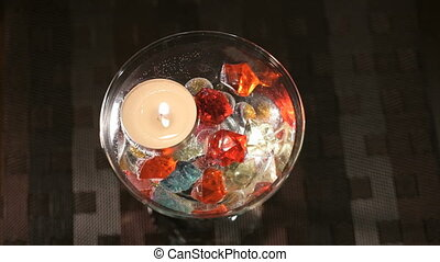Burning candle in a glass scattered gemstones. Offer hands...