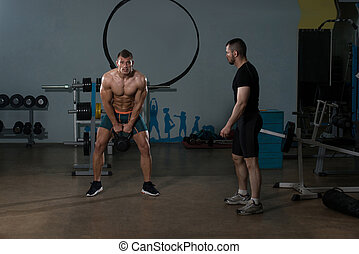 Man Working Out Kettle Bell With Personal Trainer - Handsome...