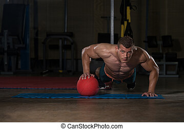 Young Man Doing Press Ups On Medicine Ball - Young Adult...