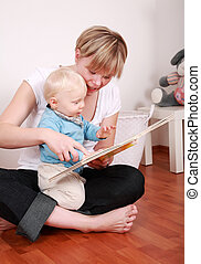Reading with mom - Cute little boy looking at picture book...