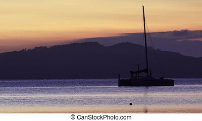Silhouette of a sail yacht at Sunrise light.