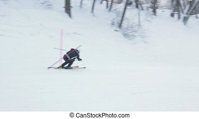 Close-up skier skiing downhill in forest