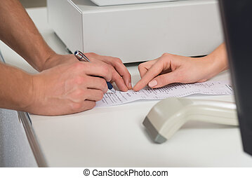 Customers Hands Signing On Receipt At Counter In Store -...