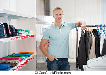 Confident Salesman Leaning On Rack In Clothing Store