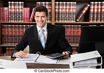 Confident Lawyer Using Calculator At Desk - Portrait of...