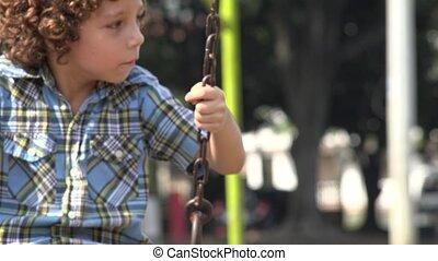 Boy Swinging on Swing Set