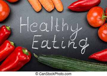 Healthy Eating Written Amidst Vegetables On Blackboard -...