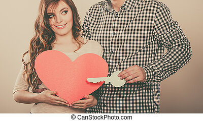 Couple with paper key to heart love symbol. - Smiling young...