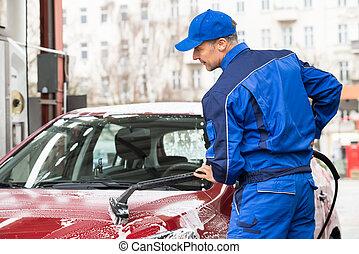 Manual Worker Washing Car At Service Station - Mature manual...