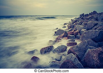Vintage photo of rocky sea shore at sunset