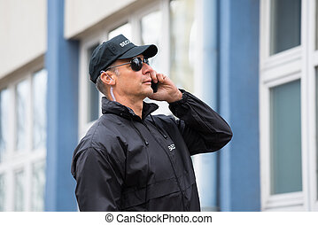 Security Guard Using Mobile Phone Outside Building - Mature...