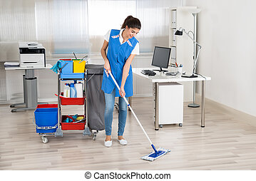 Happy Female Janitor Mopping Floor In Office - Full length...