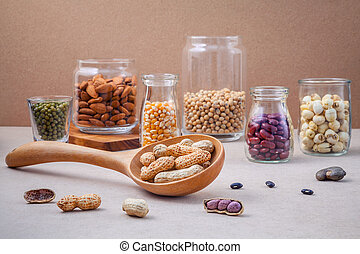 Various beans and nuts in the glass on brown background -...
