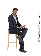 dark complexion business man using tablet while sitting
