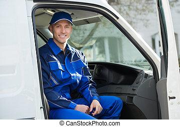 Portrait Of Happy Technician Sitting In Van - Portrait of...