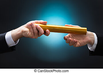Businessman Passing Relay Baton To Colleague - Cropped hand...