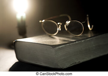 Ancient book lit by candle and old glasses on top
