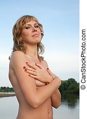 Topless blonde girl against river and sky