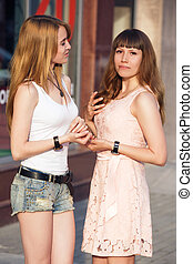 Two cheerful girls stand and speak to each other