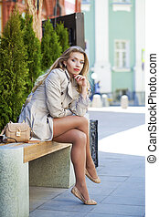 Young beautiful girl in a beige coat sitting on a bench in...