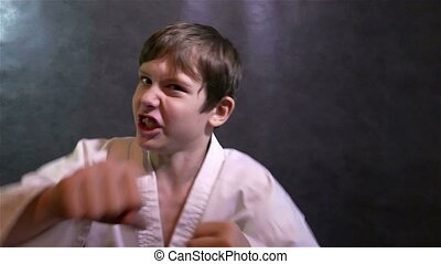 karate boy fighting kid punches at the camera slow motion
