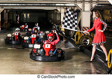 Group of people is driving go-kart car in a playground...